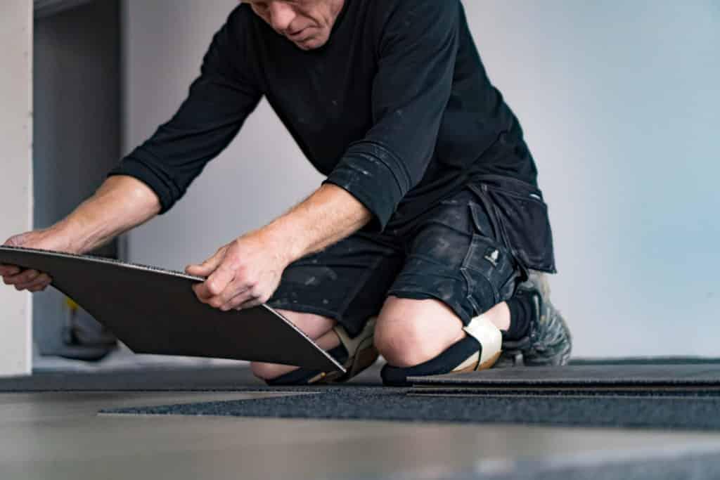 et billede af en mand fra A10 tæpper som er ved at lægge tæppefliser på et gulv