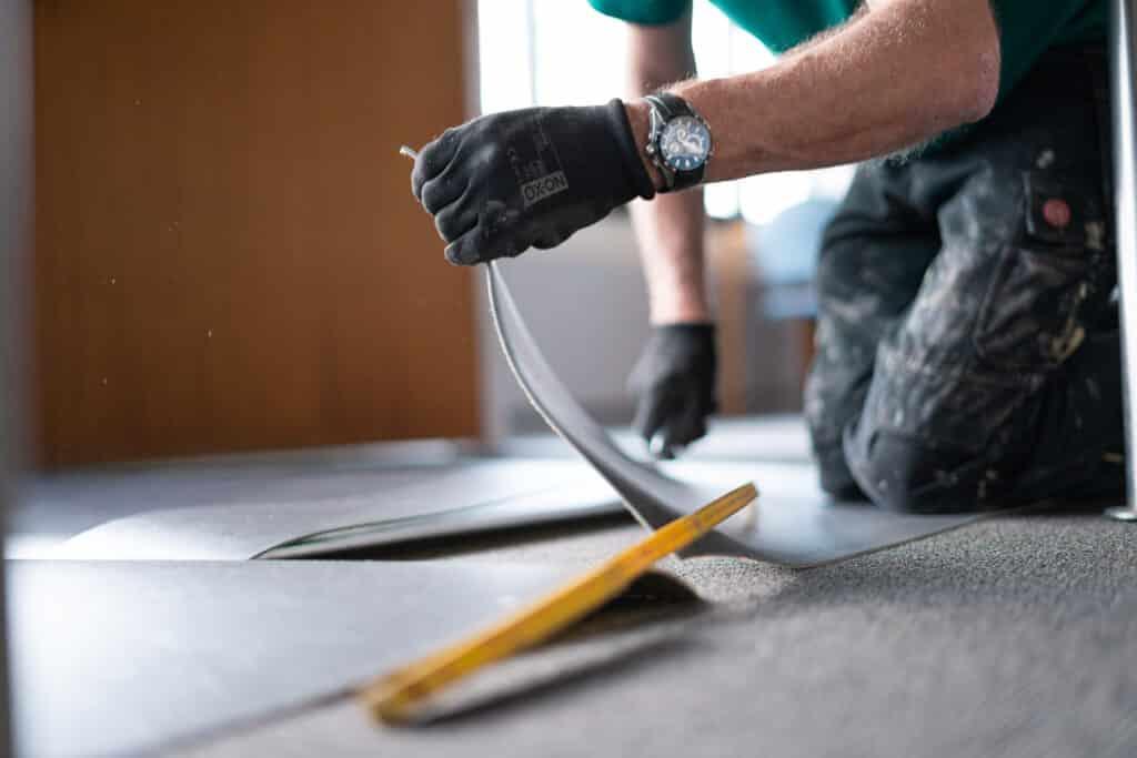et billede af en mand som skærer et linoleumsgulv