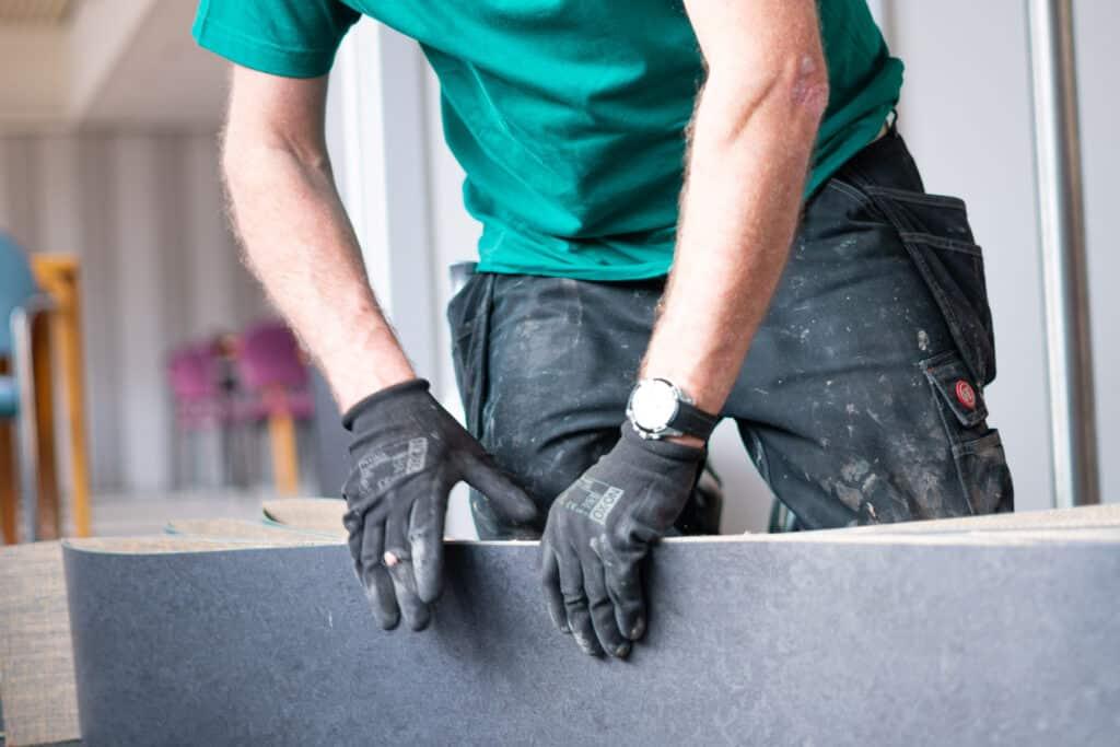 en mand som er ved at transportere linoleum hen til et andet sted for at lægge et linoleumsgulv